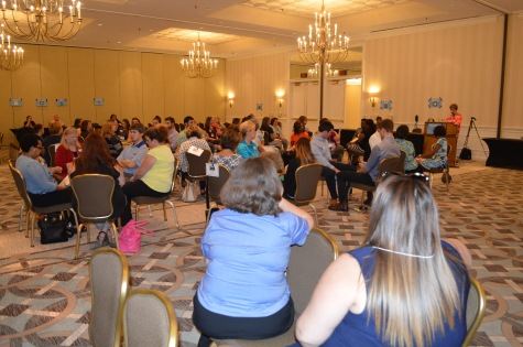 The 50 credit union staff were randomly organized into families with varying life situations and roles. Here, they are receiving their instructions prior to beginning the simulation.